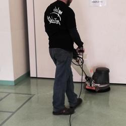 Employé Melko Nettoyage qui nettoie le sol