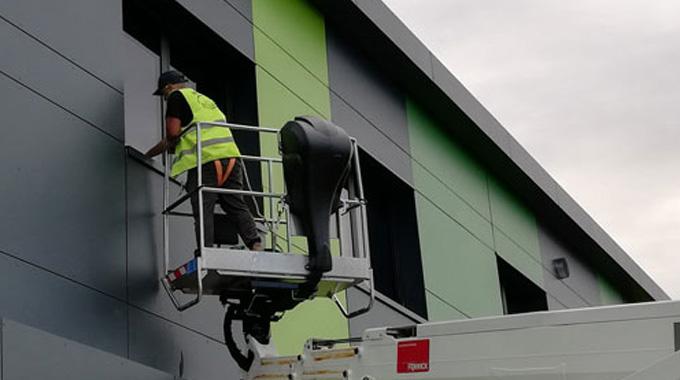 Employé Melko Nettoyage qui nettoie une vitre à partir d'une nacelle