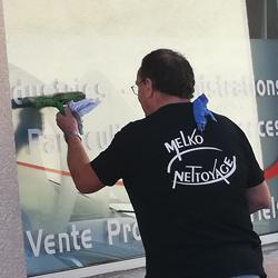 Employé Melko Nettoyage qui nettoie une vitre