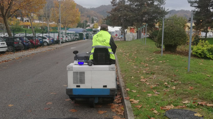Homme qui nettoie la route avec un appareil de nettoyage