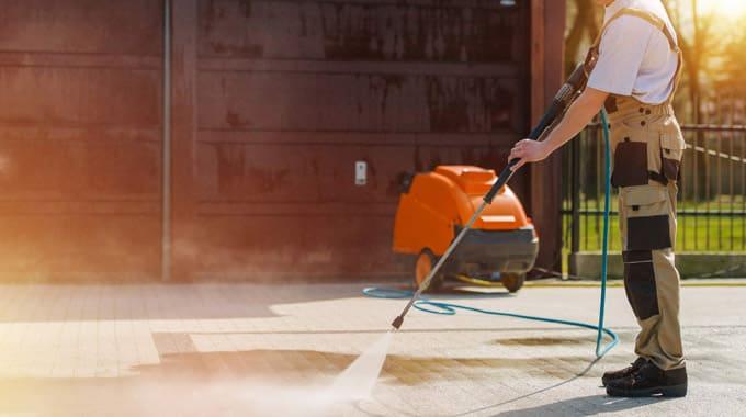 Employé Melko Nettoyage qui nettoie le sol avec une buse à haute pression
